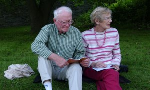 An older couple sitting on a grass bank